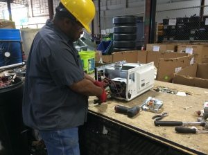 A RecycleForce employee takes apart a television to separate the parts for recycling.