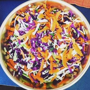 Food prepping an oriental chicken salad made with red and green cabbage, carrots, green onions, pineapple, chicken and homemade Apple Cider Vinegar dressing.